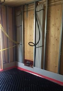 VMC con controllo deumidificazione integrato. Particolare delle tubazioni che scorrono nell'intercapedine tra la parete in legno e il tamponamento in cartongesso