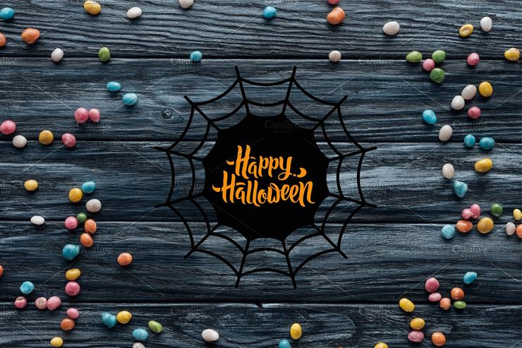 Colorful Delicious Candies on Wooden Background with Spider Web and Happy Halloween Lettering Web3Canvas