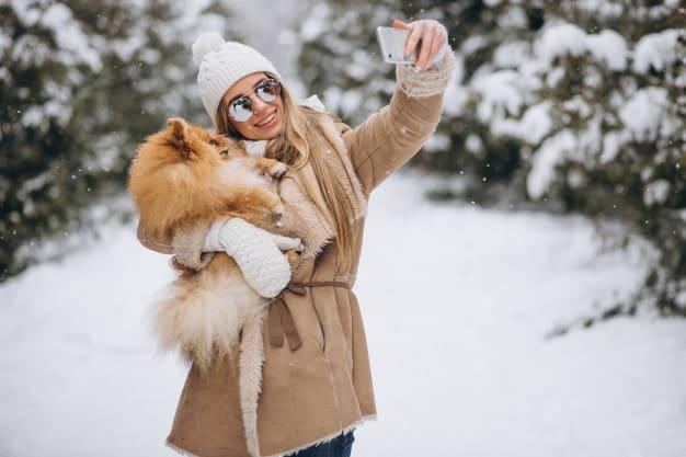 Mulher com o cachorro no colo tirando foto