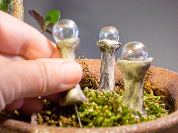 You could make them with golf tee and marbles.  Fairy Garden Gazing Balls by laughingorangestudio on Etsy,