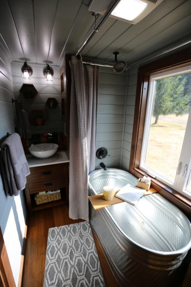 Luxurious tiny bathroom features a full-sized galvanized soaking tub, a relaxing station, spa shower, vess