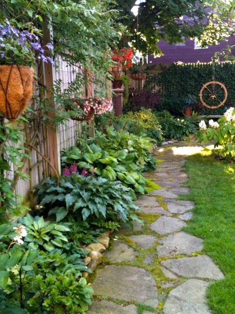 shady side of house plantings… hosta, astillbe, ferns, & more…. stone instead of grass- starting at dr