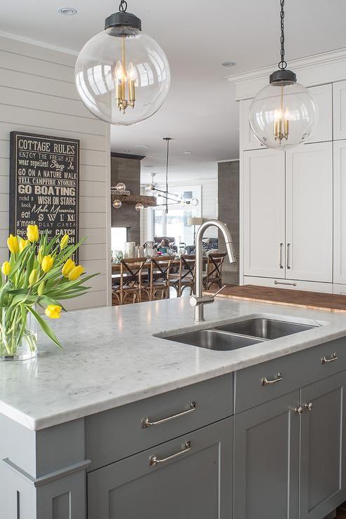 Two Regina Andrew Large Globe Pendants illuminate a gray kitchen island topped…