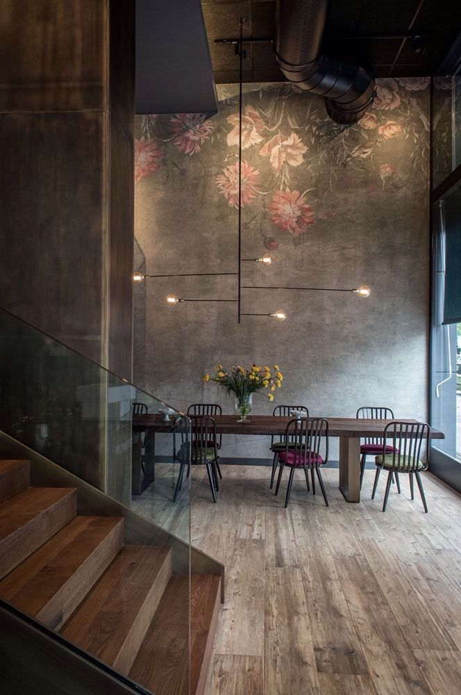 the high ceilings in concrete softened with a delicate pretty mural + unpolished wood flooring and sta