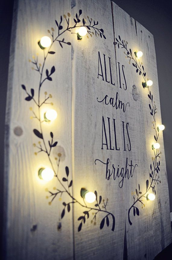 This hand-painted All is Calm All is Bright sign with lighted wreath on whitewashe