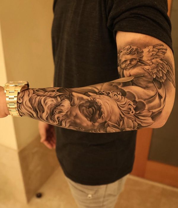 Well detailed sleeve tattoo, you can see a statue that resembles a young angel. Below him is another image which is a face of a