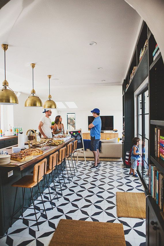 Black and white kitchen tiles with oversized brass pendants above the island. Love the leather barstools and built in bookshelves.