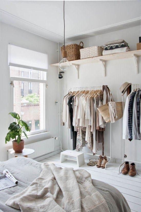 Love this minimalist and feminine Scandinavian styled bedroom with painted white wood floors, white clothing racks, Roman blinds,