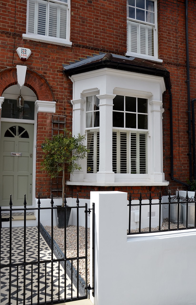 Plastered rendered front garden wall painted white metal wrought iron rail and gate victorian mosaic tile path in black and white