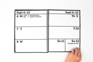 A photo of a hand turning the page of an spiral-bound calendar. The dates are printed with large, black, bold text.