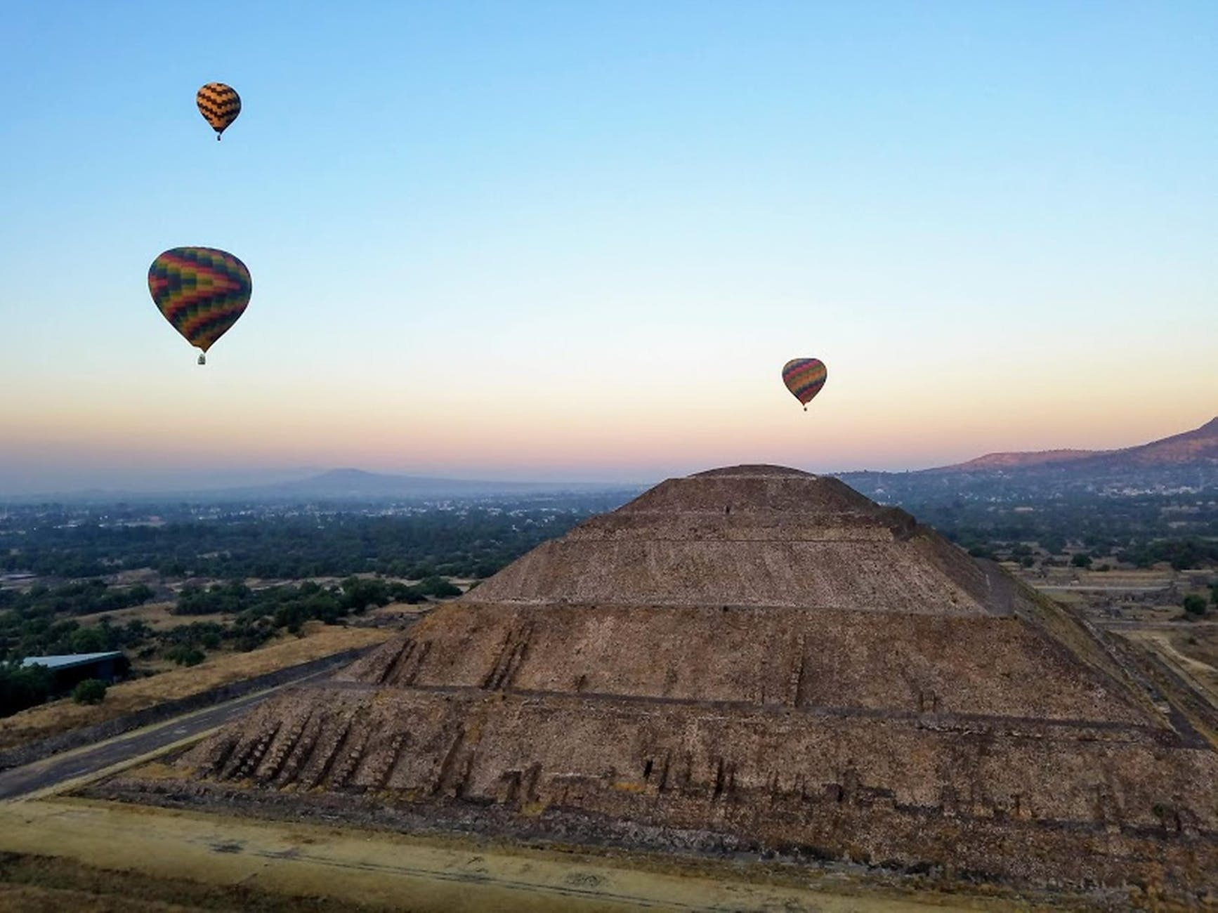 ancient pyramid of sun under flying air balloons in teotihuacan