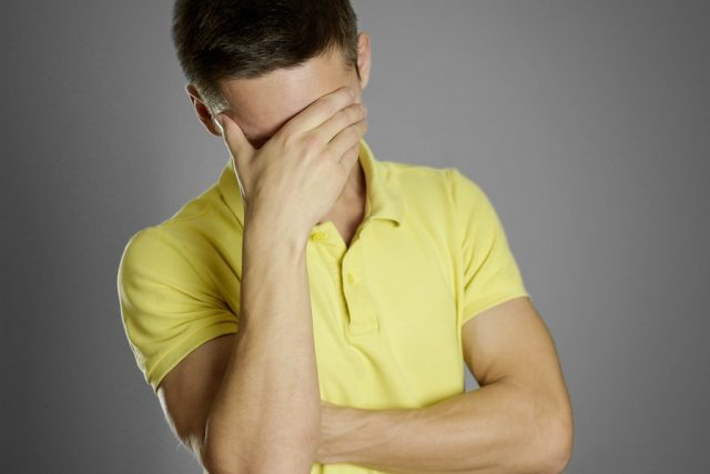 Man covering his face wearing a yellow shirt