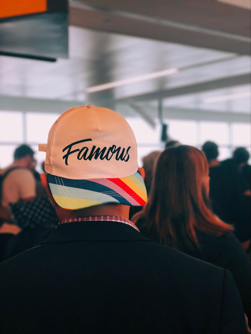 Man in cap with the word famous printed on it