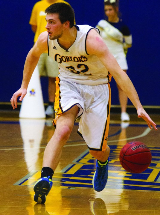 Senior center Jarrod Huskey advances the ball down the court during a December 2013 game against Greenville College (Ill.). PHOTO BY HOLLY SWAN