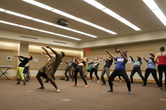 Choreographer Dominique Price runs the cast of Rocky Horror Picture Show through a warm-up in the Emerson Library Conference Room Nov. 24. The performance will take place Dec. 5 in the Loretto-Hilton Center. (Photo by Miranda Kenny)