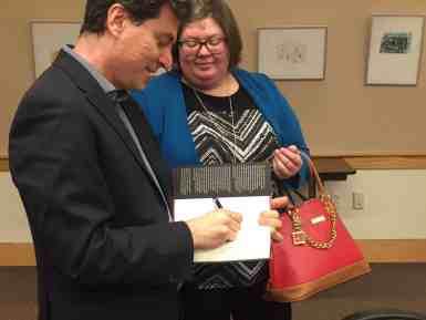 """Vicken Cheterian signs copies of his book, """"Open Wounds."""" JAZMINE O. JONES/The Journal"""