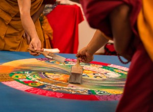 Buddhist monks swirl sand with paint brushes at the beginning of the dissolution ceremony.   Photo by Sara Bannoura