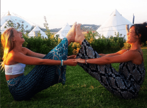 Benassi practicing yoga with another yoga student in Spain, 2015.