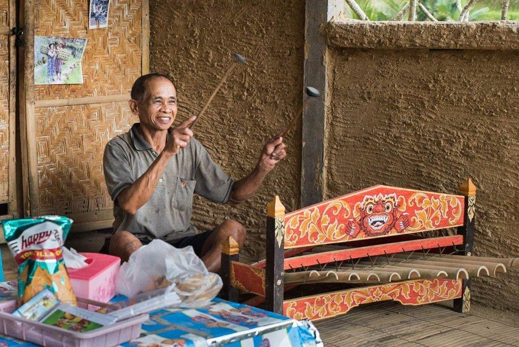 Hombre balinés tocando un instrumento musical en las terrazas de arroz de Tegallalang - Bali, Indonesia