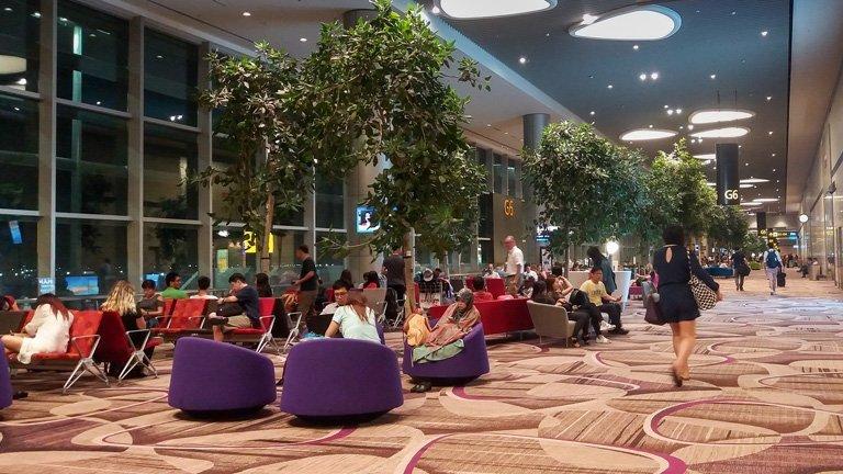 Viajeros esperando su vuelo en el aerupuerto Changi, Singapur