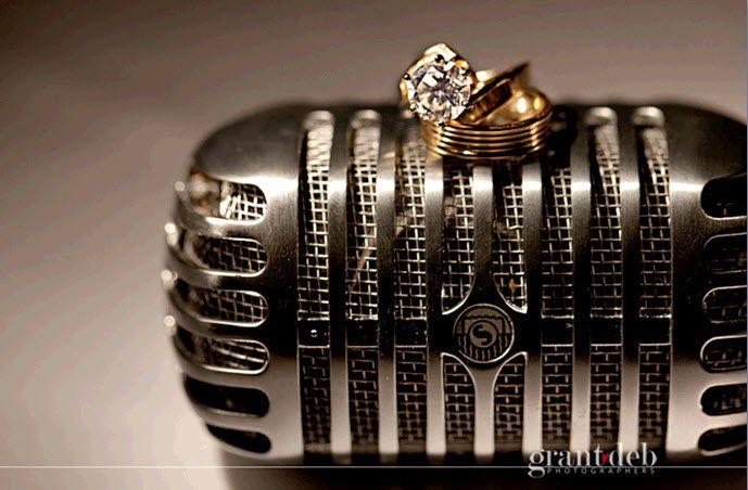 artistic-wedding-detail-shot-gold-wedding-bands-diamond-engagement-ring-sit-atop-vintage-microphone
