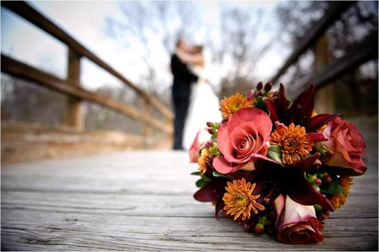 Stunning fall bridal bouquet with pink roses and orange and maroon flowers sits on wood dock brid