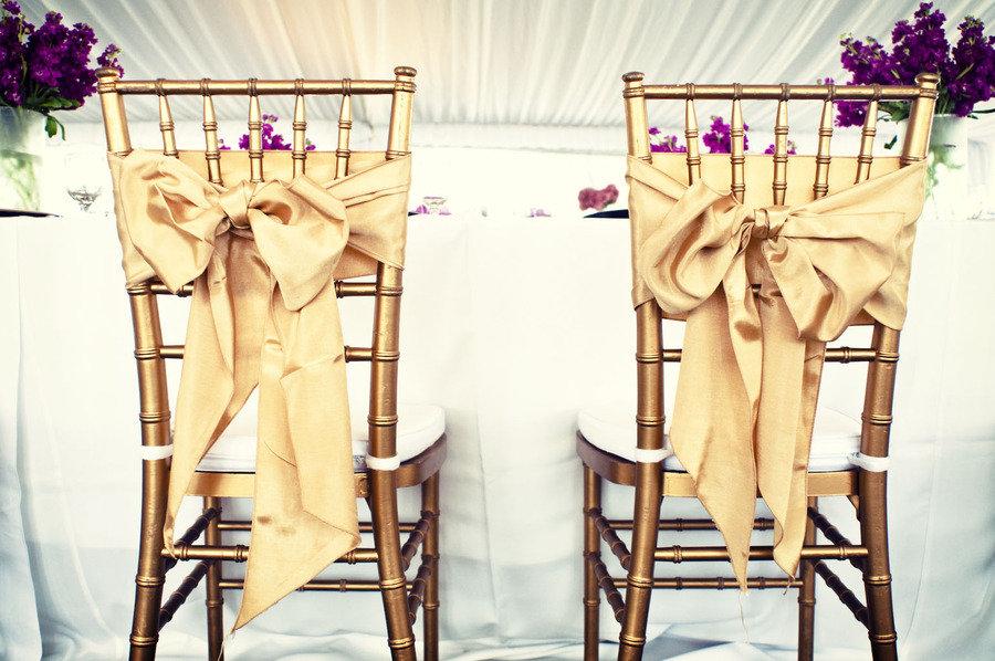 Elegant wedding reception bride groom chairs gold bows onewed com