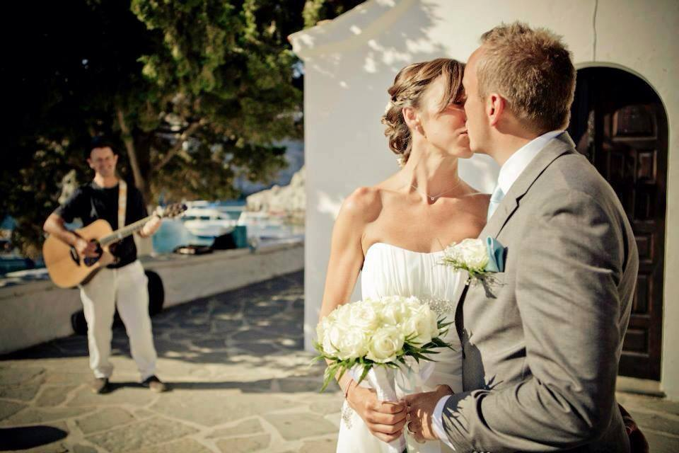 A newly wed couple kiss in front of a Greek chapel. In the background you can see the sea and Mark Usher, Musician and Wedding DJ in Rhodes, Greece playing the guitar.
