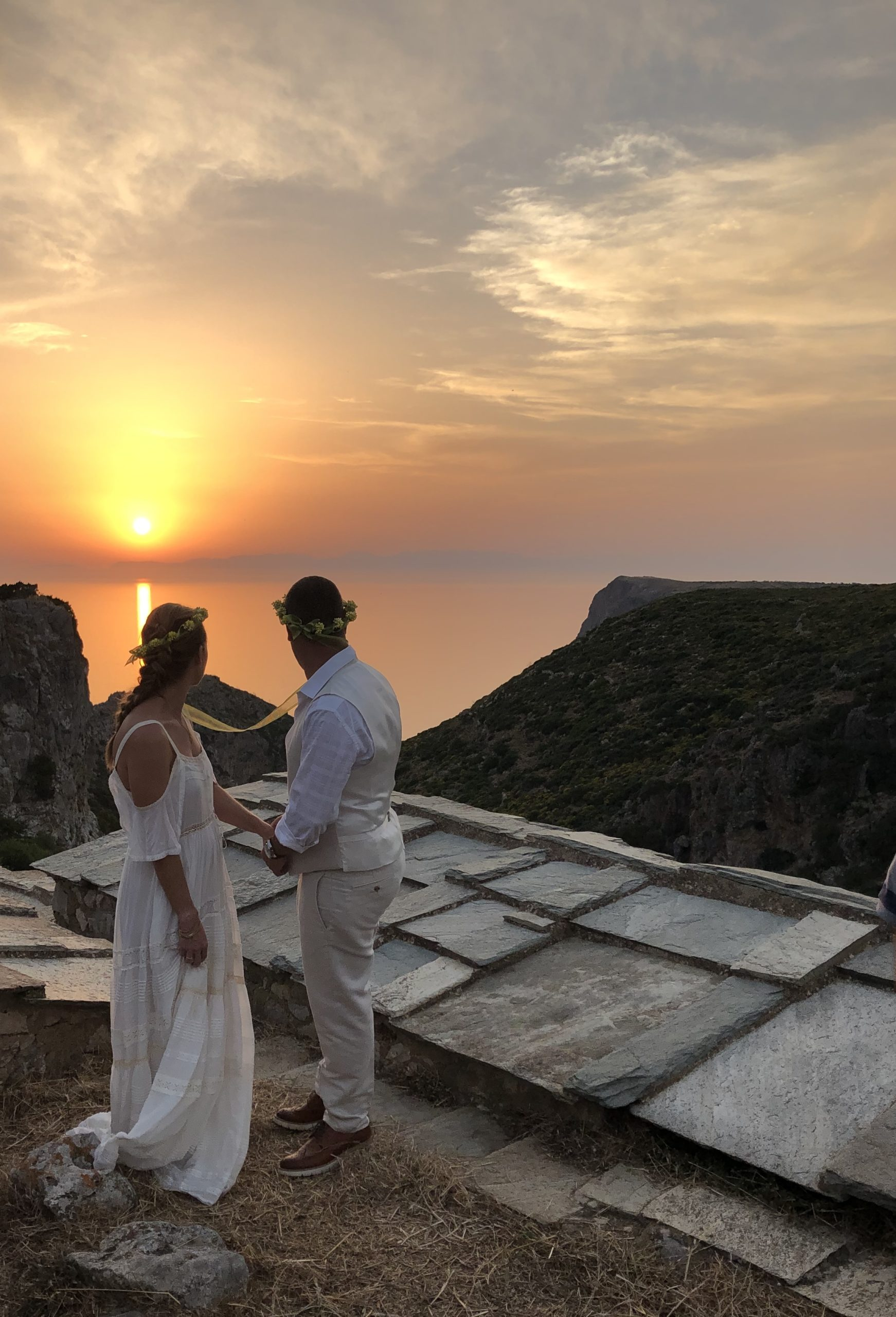 A couple watch the sunset in Kythira at the end of their Celebrant wedding ceremony. They are wearing Greek wedding crowns made from Sempre Viva