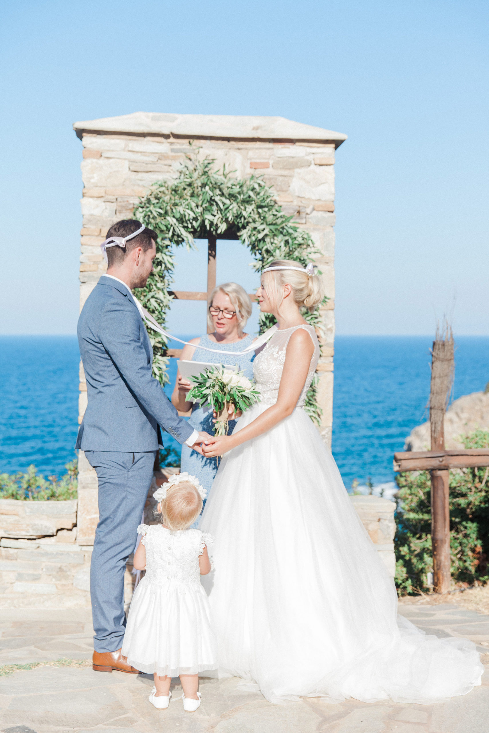 A wedding ceremony with the couple and their wedding celebrant in Greece. The couple are wearing Greek wedding crowns.