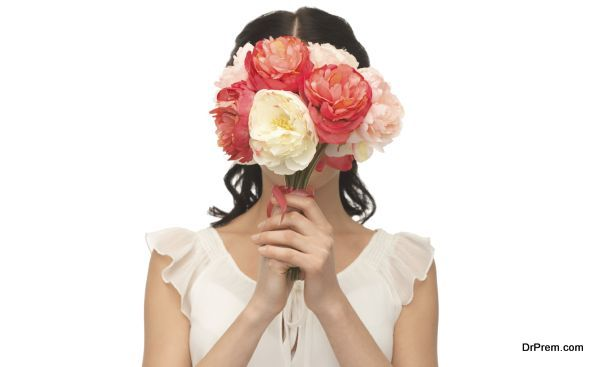 woman holding bouquet of flowers over her face