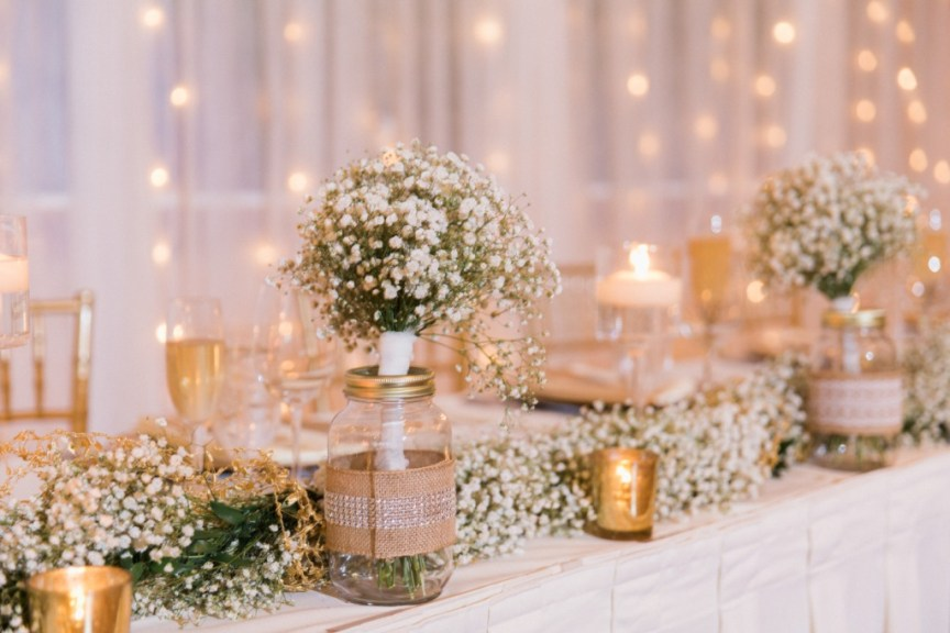 Head table with garland from gazebo and bridesmaids' bouquets