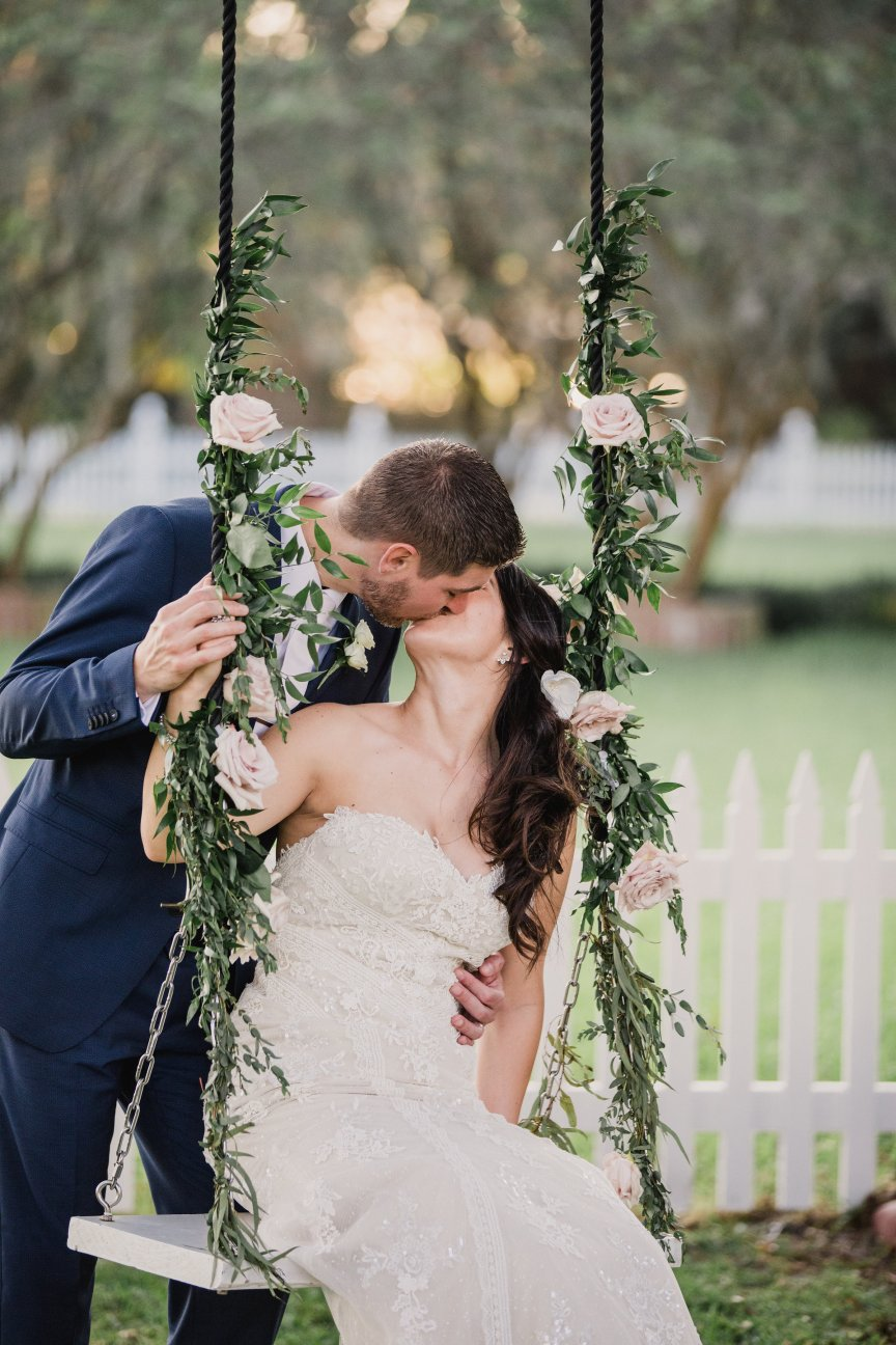 Bride and Groom Kissing on Swing