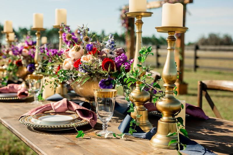 Close Up of Guest Table Centerpieces with Gold Candles