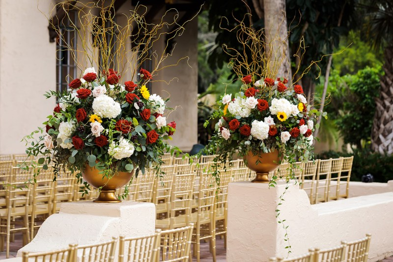 Floral Arrangements in Golden Urns at Back of Aisle During Wedding Ceremony