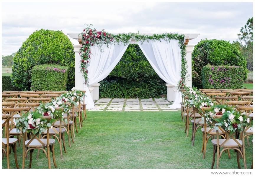 Ceremony Site with flowers, greens, and draping on pergola and aisle flowers on chairs