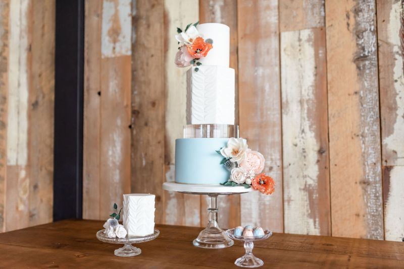 Four tier wedding cake by Anna Lewis Cake Design in white and blue with a modern acrylic tier and intricate sugar flowers. Research your suppliers online whilst planning during covid-19
