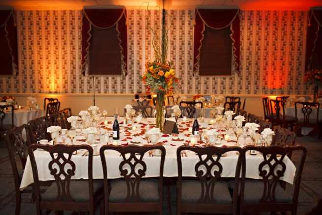 kings table at wedding reception with fall decor