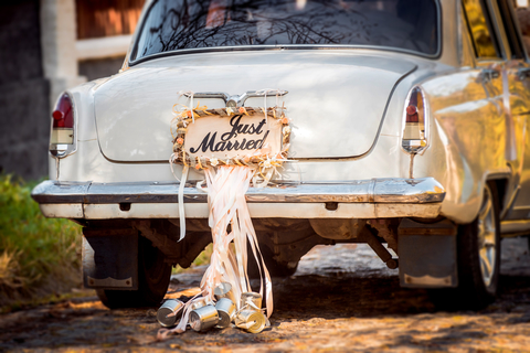 decorate newlyweds car - just married sign and tin cans on back of car