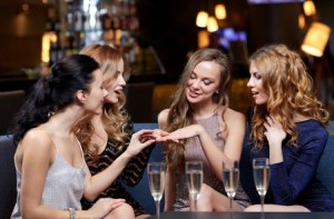 51892952 - celebration, friends, bachelorette party and holidays concept - happy woman showing engagement ring to her friends with champagne glasses at night club