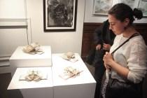Artist Kremena Stephanova looking at artist Wayne Kleppe's work.
