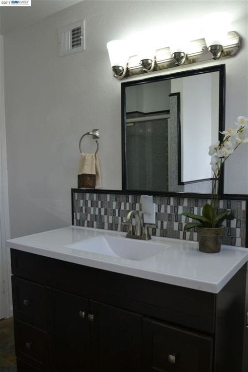 The sink backsplash matches the shower accent