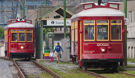 """I'm not certain what the names of these New Orleans street cars are, but I'm willing to bet it's not """"Desire."""" These are disgorging and taking on passengers at the Toulouse Stree stop in the French Quarter."""