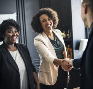 two black women smiling and shaking a man after a lesson on negotiation