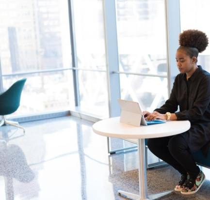 a black lady checking her laptop for tips on how to combat loneliness