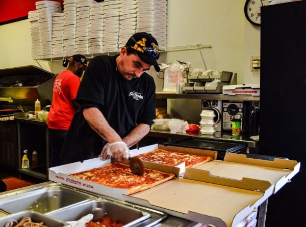 "Employee Jeff Alderman slices ""whole tray"" orders in the downtown Wheeling store."