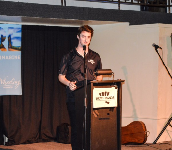 """Jake Dougherty, director of ReInvent Wheeling, informs the large crowd about how """"Show of Hands"""" works."""