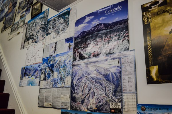 One wall in the shop is covered with trail maps from the mountains Exley has visited.