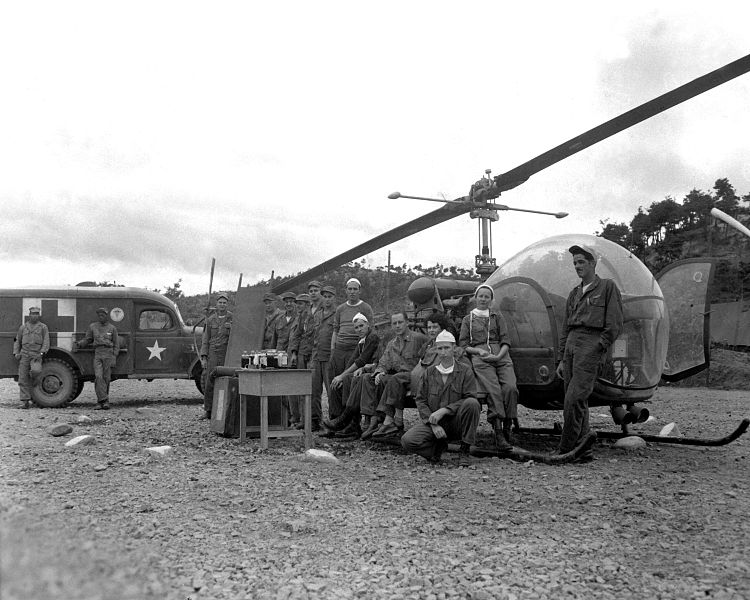 8225th MASH personnel posing with the type of helicopters they would use to evacuate wounded, 1951