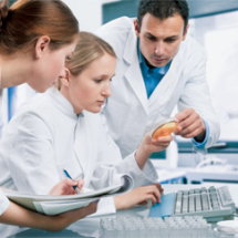 Researchers at computer in lab coats
